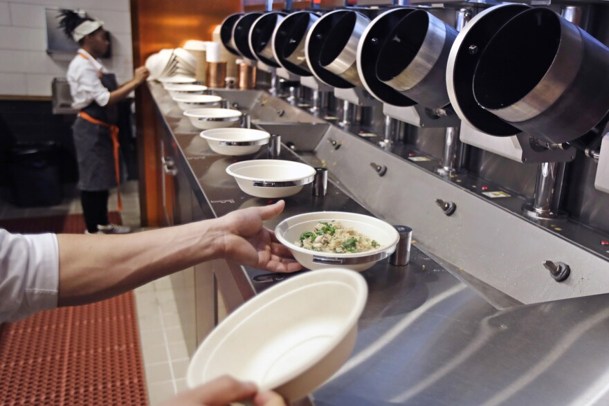 "A worker lifts a lunch bowl off the production line at Spyce, a restaurant which uses a robotic cooking process, in Boston, Thursday, May 3, 2018. Robots can't yet bake a souffle or fold a burrito, but the new restaurant in Boston is employing what it calls a ""never-before-seen robotic kitchen"" to cook up ingredients and spout them into a bowl. (Charles Krupa/AP)"