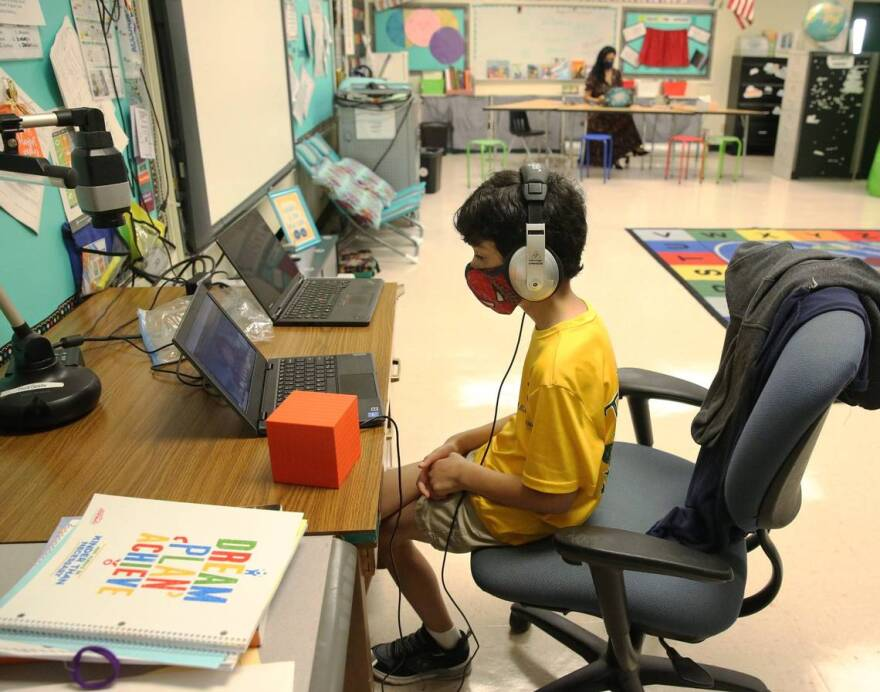 A young boy wearing a face mask and headphones sits in front of a laptop in an empty classroom with a teacher.