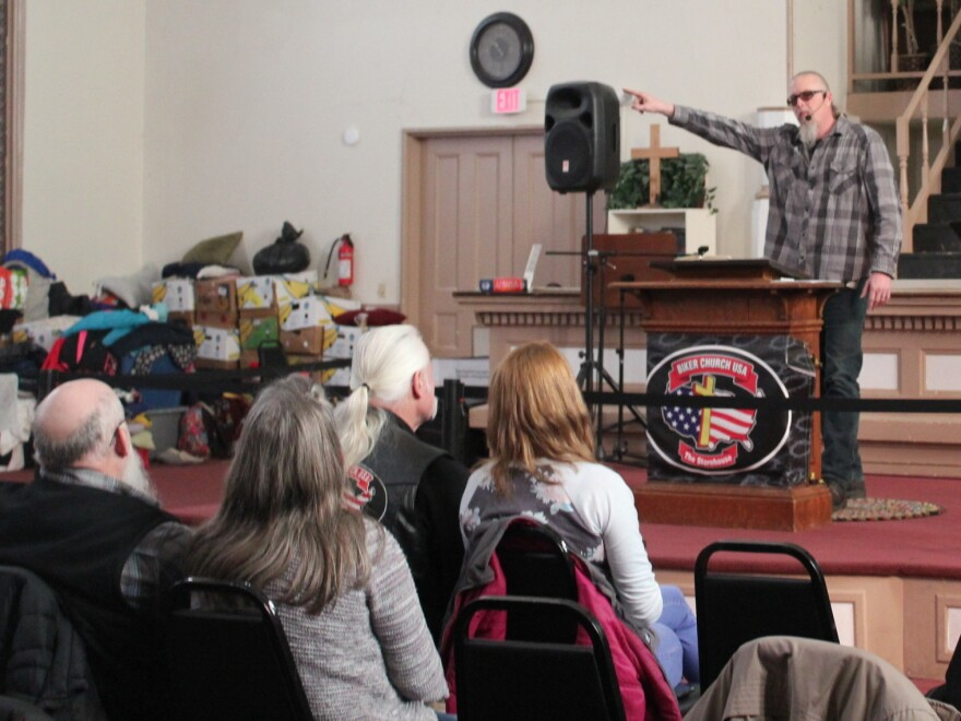 Pastor Tim Theriault preaches during a Sunday morning service at Biker Church USA, housed inside a large brick building in Bangor, Maine. The church purchased the building this year and has turned it into a warming shelter for homeless residents.