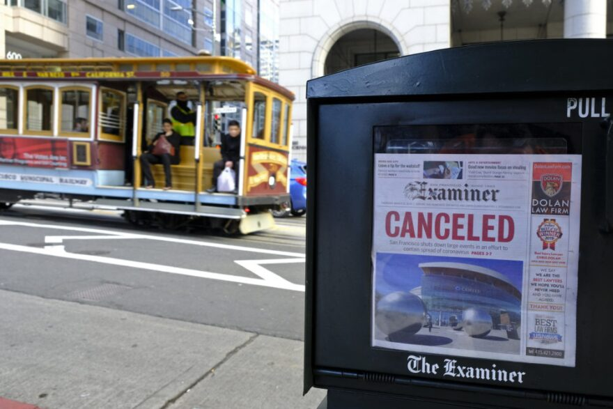 A newspaper headline announcing the closure of large events is displayed as a cable car goes down California Street, Friday, March 13, 2020, in San Francisco. (Eric Risberg/AP Photo)
