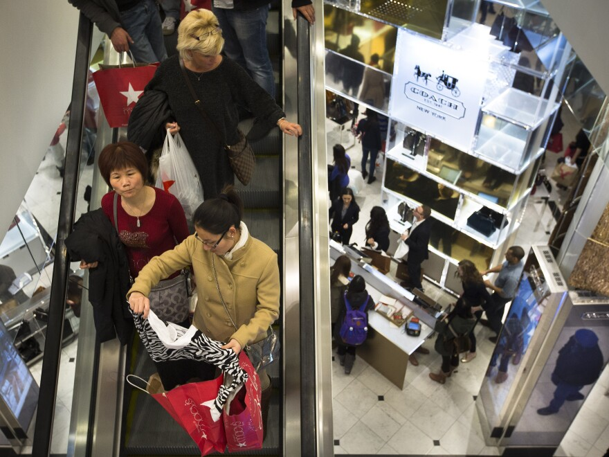 Shoppers crowd a Macy's store in New York on Thursday. Many retailers stayed open on Thanksgiving Day this year, a new holiday tradition that analysts say is here to stay.