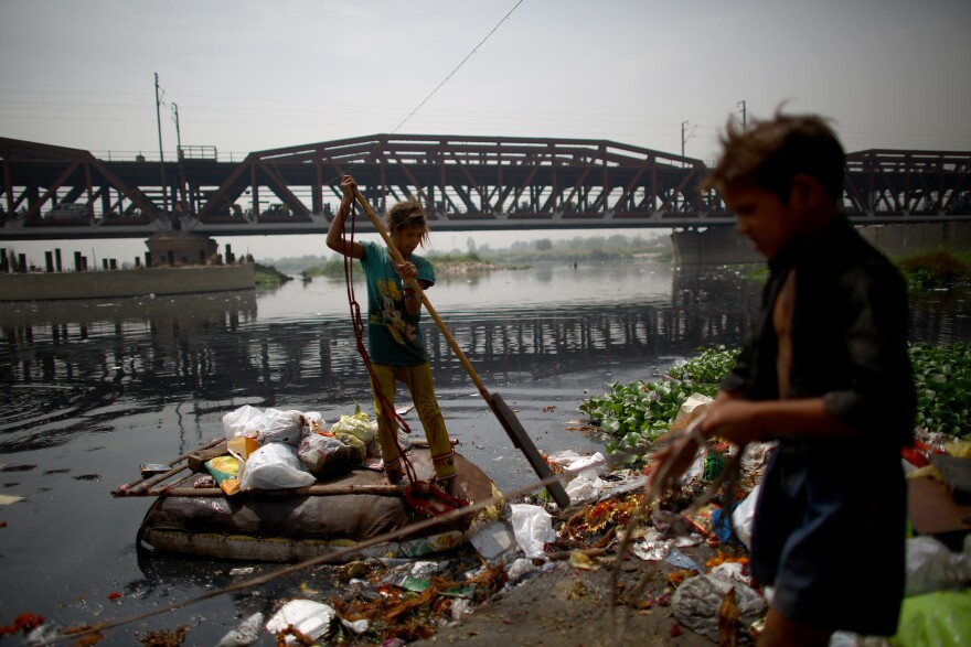 In the shadow of the British colonial Old Iron Bridge, children ply the Yamuna River in makeshift rafts and scour its banks in search of anything valuable to help their families eke out an existence.