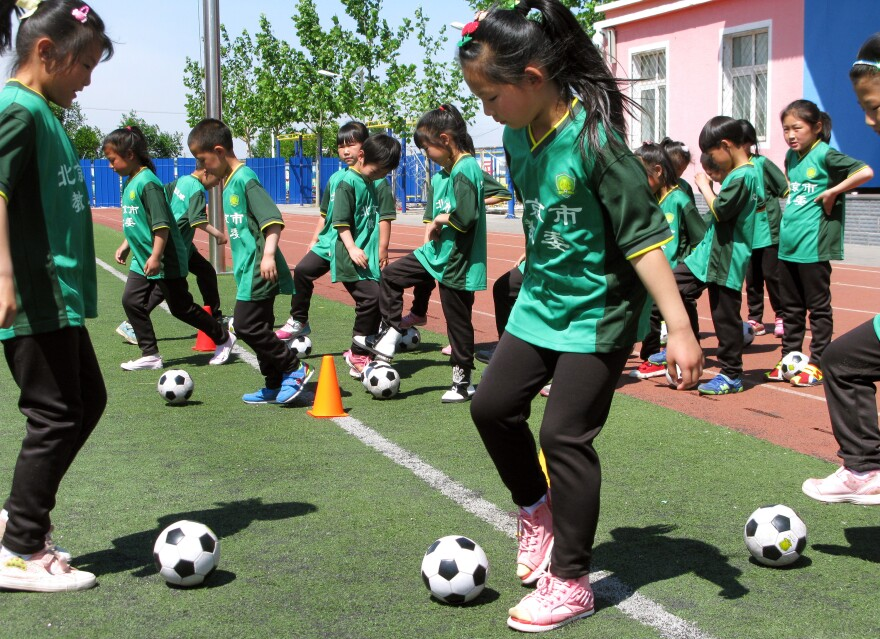 First-graders take soccer class at the Nandulehe Elementary School in suburban Beijing. The school is one of 20,000 that's launching a national soccer curriculum in the next five years. It's part of a government plan to raise China's soccer skills and eventually, China's leaders hope, host and win a World Cup.