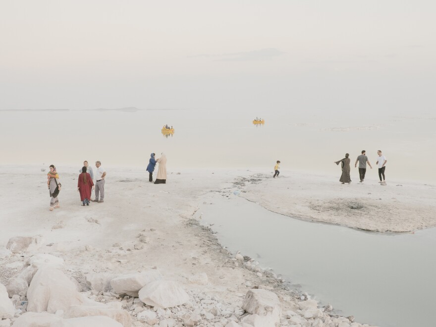 """Tourists from nearby cities like Urmia and Tabriz often visit the lake on weekends for a swim. Mann says this is his favorite photo of the group: """"You can see the people trying to enjoy it there,"""" but also see the water disappearing."""