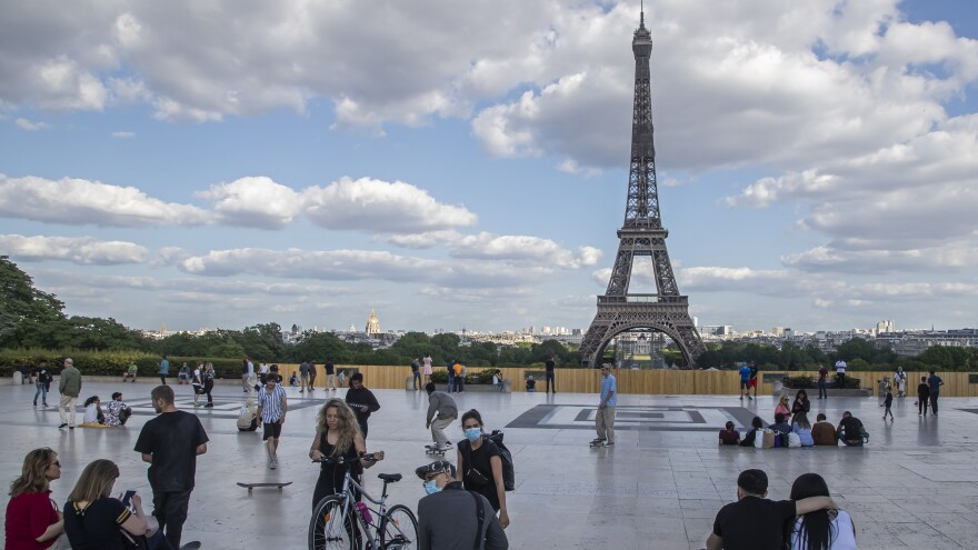 People stroll near the Eiffel Tower in Paris on Monday. France is entering its second phase of lifting COVID-19 restrictions.