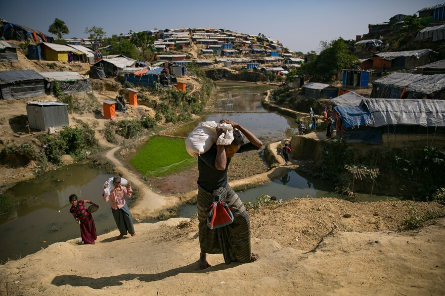 Mohamed Yonus (dark shirt, green skirt) carries his distribution bag to his home in the Hakimpara refugee camp.