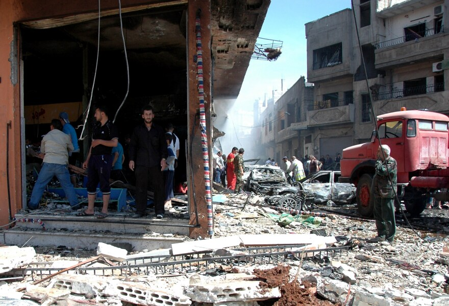 Civilians and emergency personnel inspect the site of a car bomb explosion in the Abbasiyah neighborhood of Syria's central city of Homs on April 29.