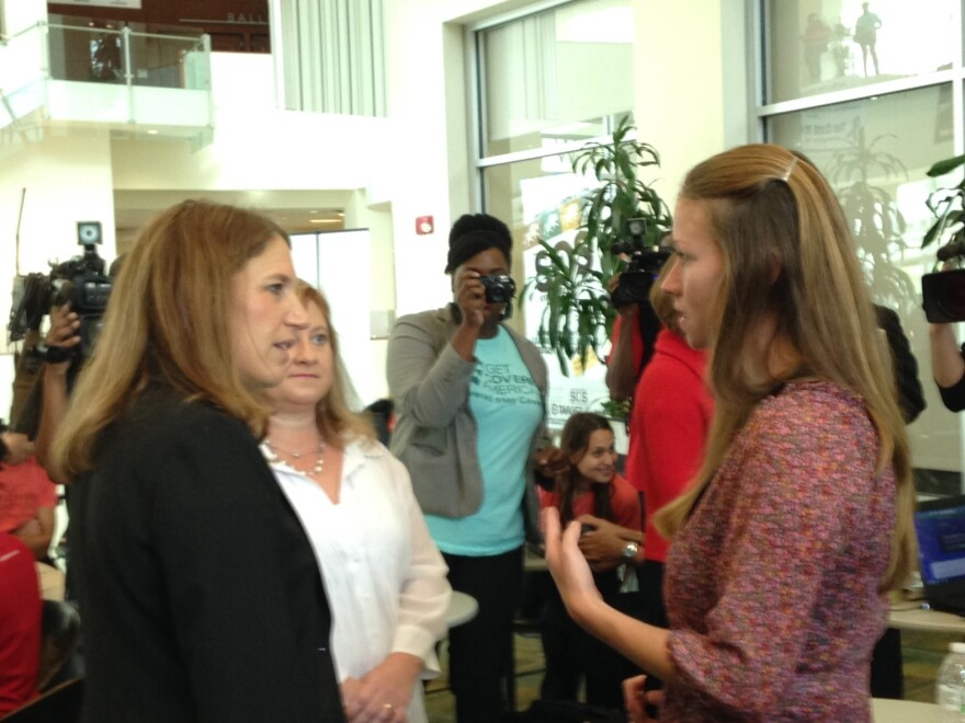 U.S. Health and Human Services Secretary Sylvia Burwell speaks with a woman enrolling for health insurance Monday at the University of South Florida enrollment event in Tampa.