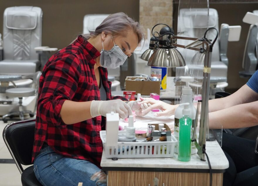 Debi Dang works on the nails of a customer in Atlanta, Georgia on April 24, 2020. Governor Brian Kemp has eased restrictions allowing some businesses such as hair and nail salons to reopen today in the US state of Georgia after a four-week lockdown to stop the spread of COVID-19.