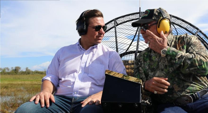 "Republican gubernatorial candidate Ron DeSantis, left, tours the Everglades on an airboat alongside former Florida Fish and Wildlife Commissioner ""Alligator"" Ron Bergeron"