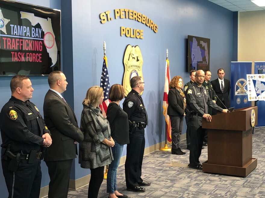 A group of law enforcement officers and community partners at the St. Pete Police station stand around a podium to deliver the news about the task force.