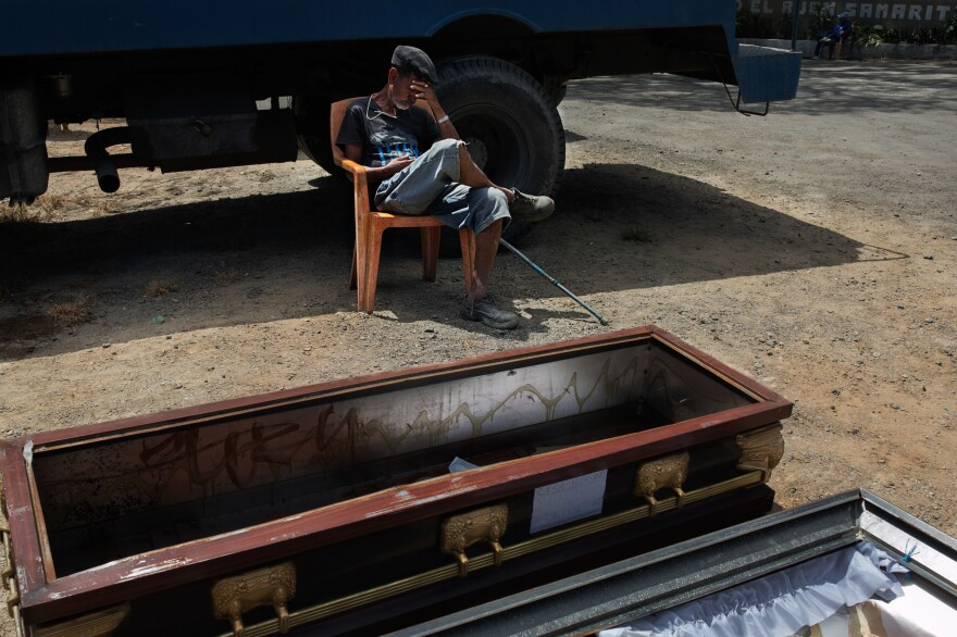 A resident naps in the front yard of the home for senior citizens. The coffin, used at funeral ceremonies but not for burial, is being aired out.