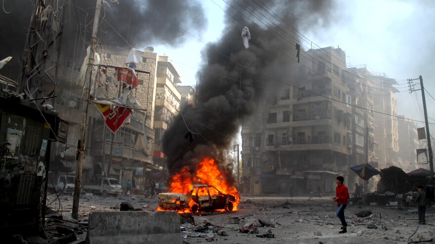 A Syrian youth walks near a vehicle in flames following an airstrike, allegedly by government forces, on April 4 in the northern Syrian city of Aleppo.