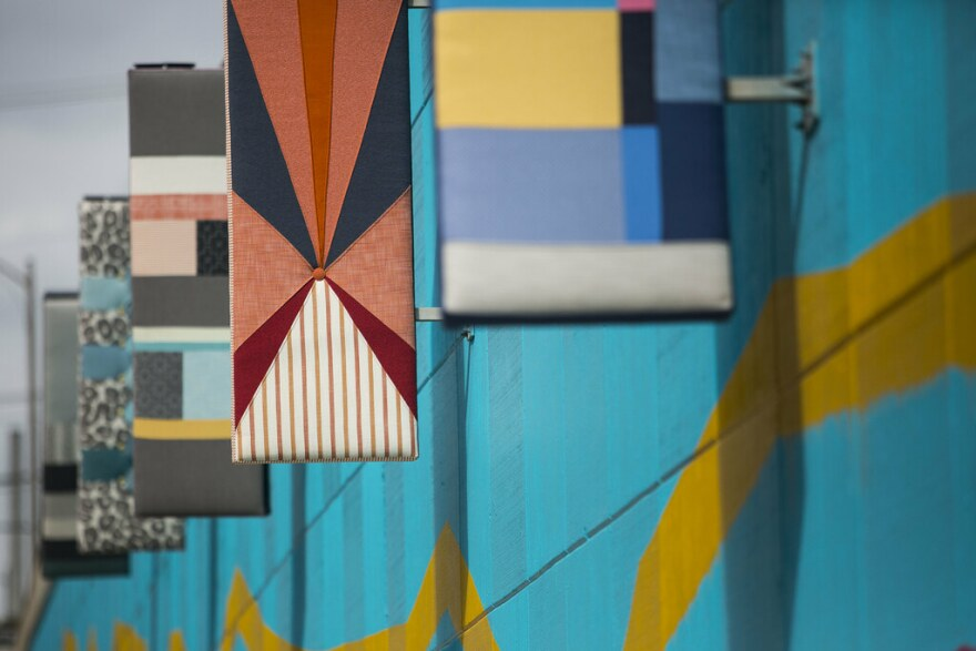 Fabric-covered panels hang on a bright teal wall with a yellow painted stripe.