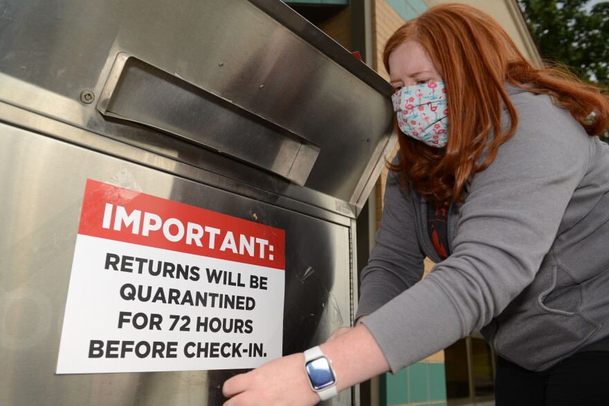 Picture of a woman wearing a face mask affixing a sign to a library book drop