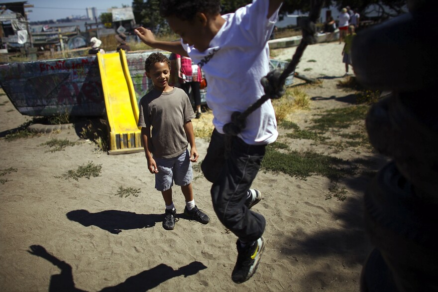 """Deion Jefferson, 10, and Samuel Jefferson, 7, take turns climbing and jumping off a stack of old tires at the Berkeley Adventure Playground in California. The playground is a half-acre park with a junkyard feel where kids are encouraged to """"play wild."""""""