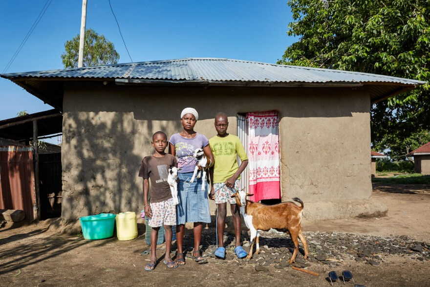 Cheryl Awuor stands by her house with sons Rolines (left) and Brian (right) in November 2019. Awuor is part of a community banking group: Members give money each week into a collective pot, take out loans in times of need and are occasionaly given a bonus: a goat (hers is pictured above). She hoped raising goats would help sustain her family but the flooding carried her livestock away.