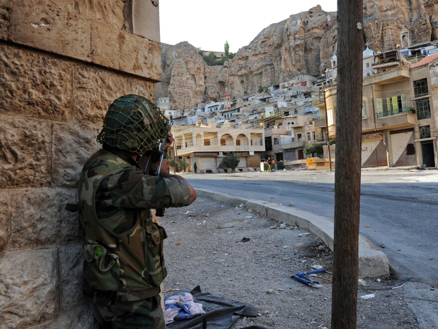 A Syrian government soldier aims his weapon during clashes with Free Syrian Army fighters in Maaloula, north of Damascus, in this photo released by the Syrian official news agency SANA in September.