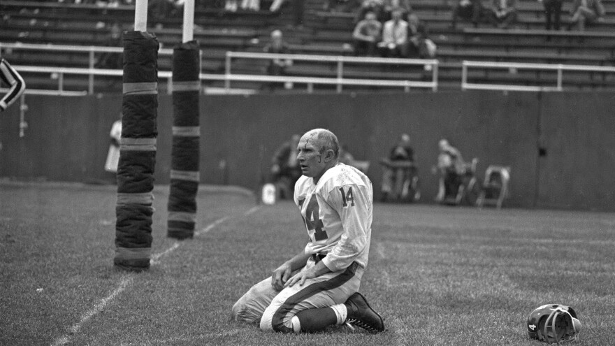 In this iconic photo from Sept. 20, 1964, New York Giants' Y.A. Tittle squats on the field after being hit hard while passing during a game against the Pittsburgh Steelers.