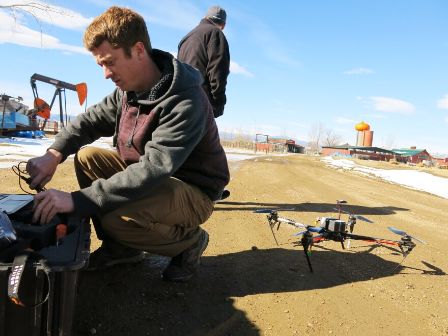 Jimmy Underhill, drone technician with Agribotix, prepares the drone's control module at a farm in rural Weld County.