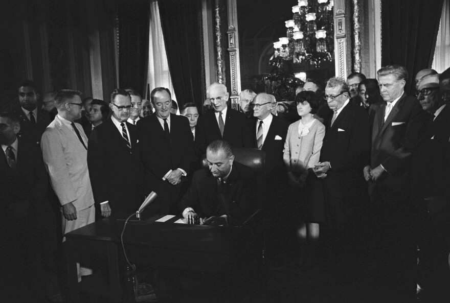 President Lyndon B. Johnson signs the Voting Rights Act.