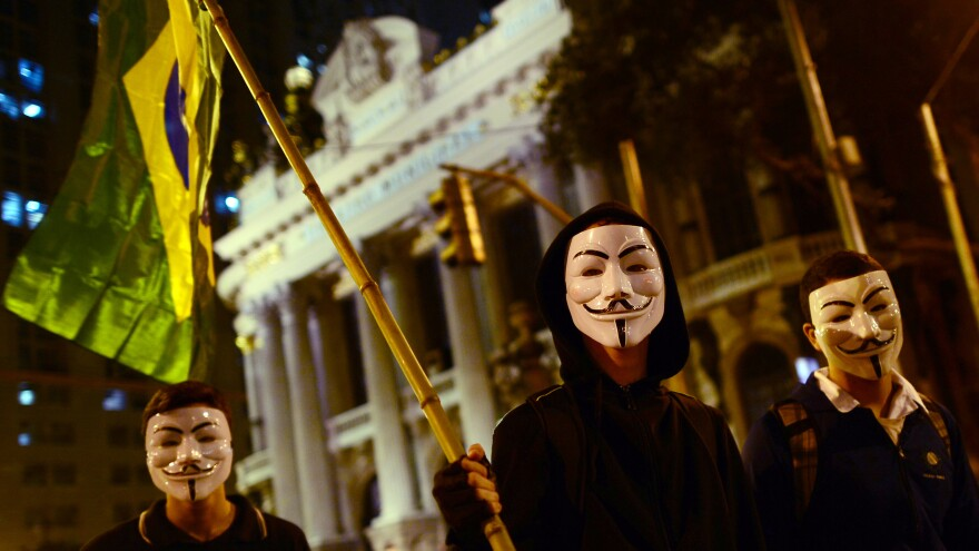 """<strong><a href=""""http://www.npr.org/blogs/parallels/2013/06/18/193101142/with-inspiration-from-turkey-brazil-discovers-mass-protests"""">Rio de Janeiro</a>:</strong> Demonstrators wearing Guy Fawkes masks and waving a Brazilian national flag march in downtown Rio on June 17 against higher public transportation fares and the use of public funds to finance international soccer tournaments."""