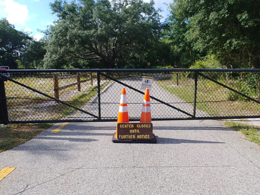 The gate of Brooker Creek Preserve is closed with two cones in front of it and a sign that states center closed until further notice.