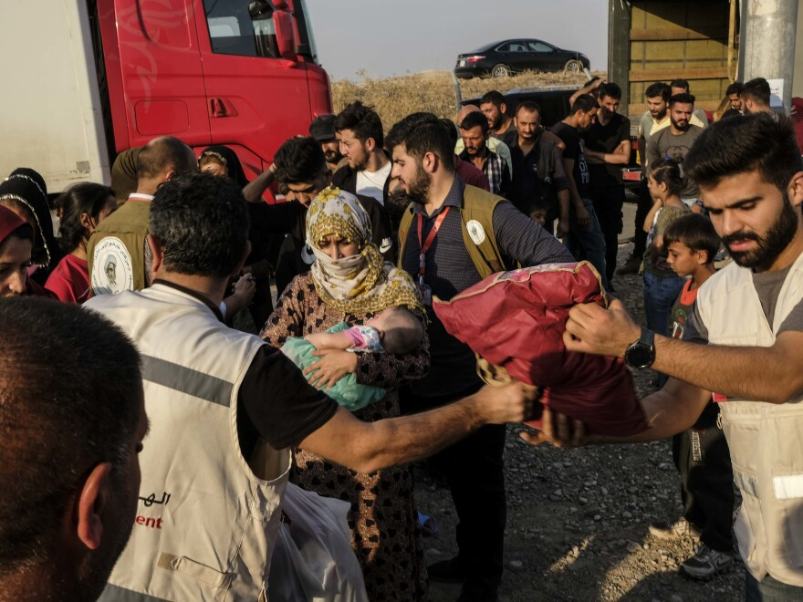 Syrians fleeing the Turkish incursion in northeastern Syria receive bedding materials as they arrive at a camp in Dohuk, Iraq, on Thursday.