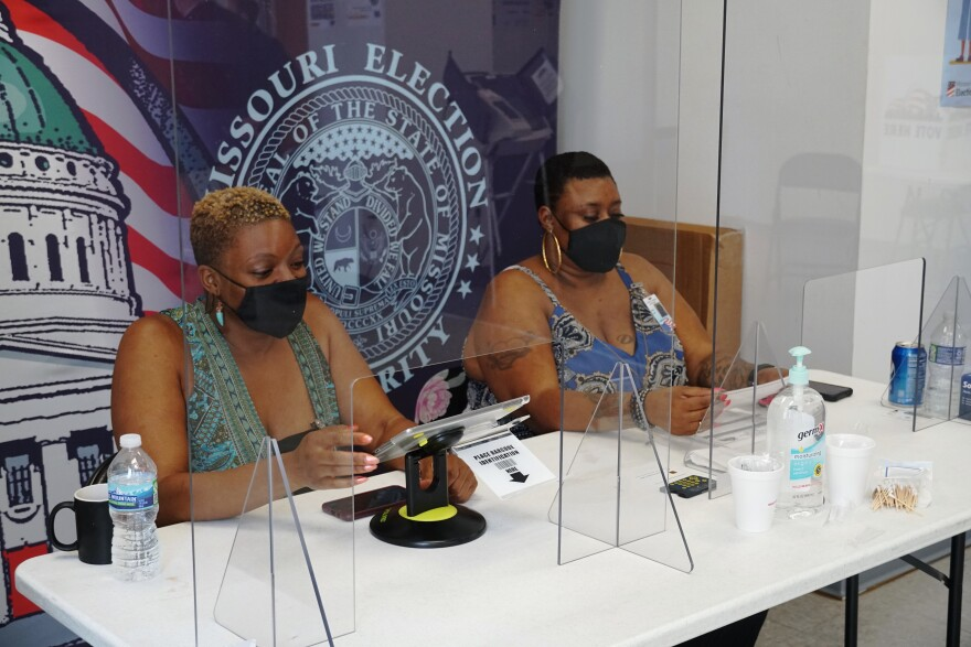 An image of two Black women, wearing face masks, sitting behind plastic shields. They are looking at iPads