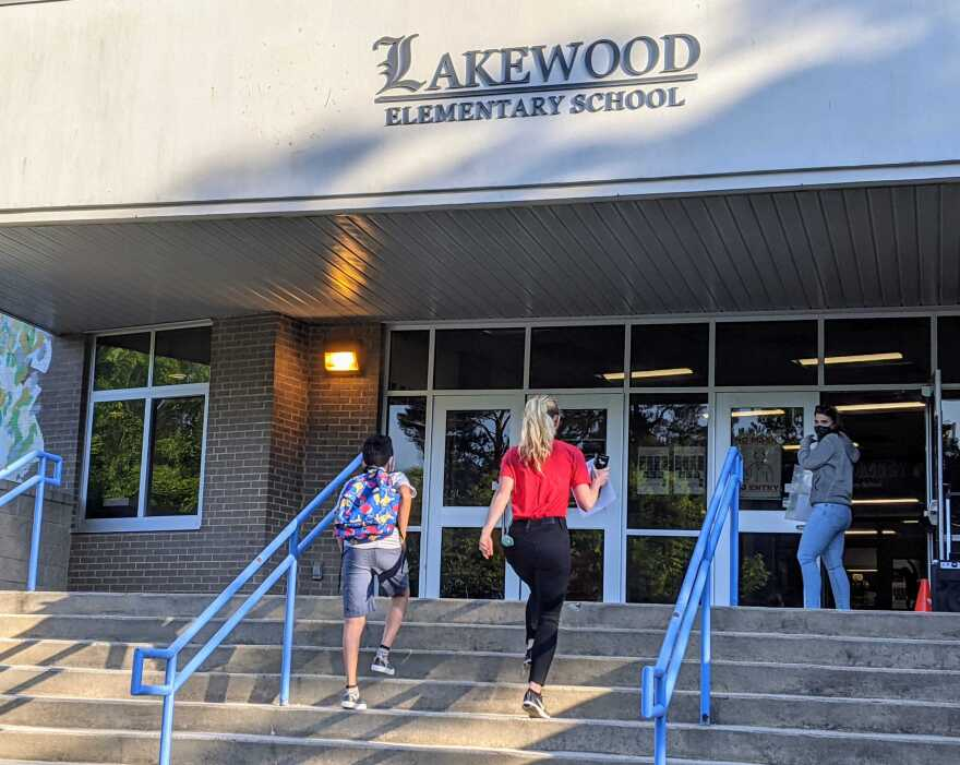 Fifth grade student Jairo is entering Lakewood Elementary School for the first time in many months with his former teacher Kelly Shearon.  After almost a full school year of virtual learning, Jairo returns to take his graduation exams.