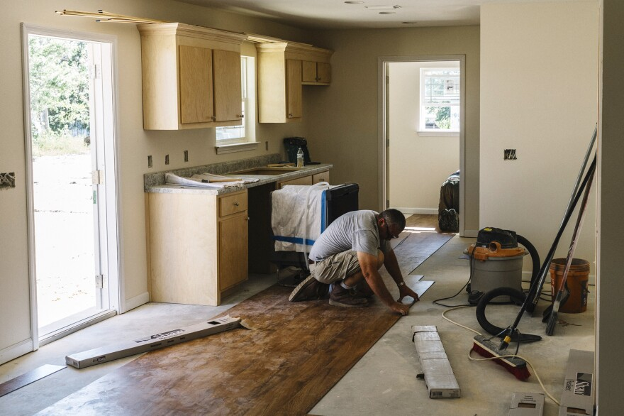 Construction manager Ross Potts installs flooring in a Habitat for Humanity home near downtown Panama City. He says relatively simple construction techniques make their homes resistant to hurricane-force winds.