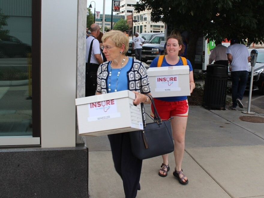 Supporters of Medicaid expansion lug boxes of petitions to the Nebraska secretary of state's office Thursday.