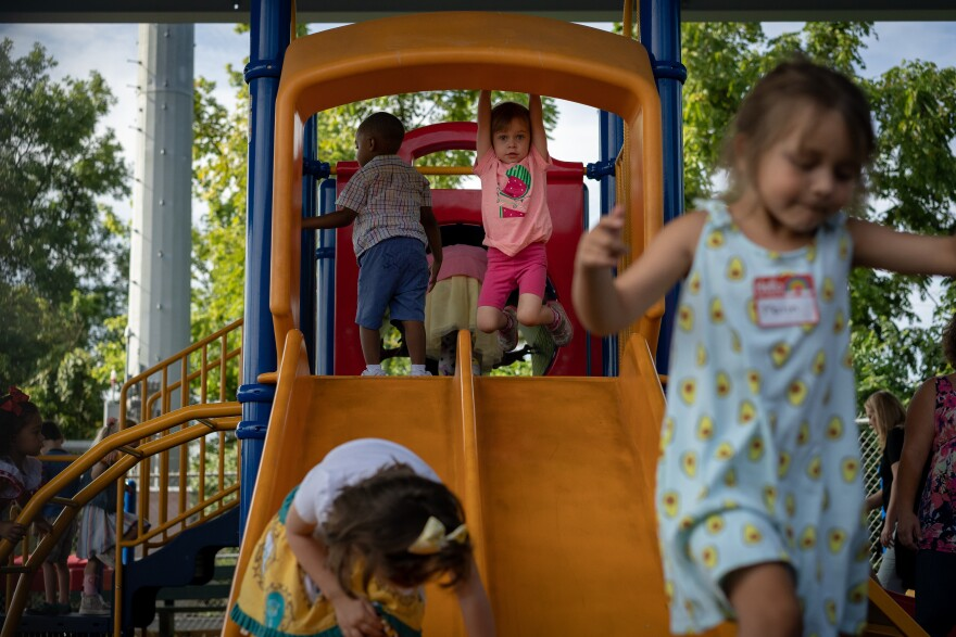 Matea Tilden hangs from the slide at the Affton Early Childhood Center Tuesday, Aug. 13, 2019, on her first day of school.