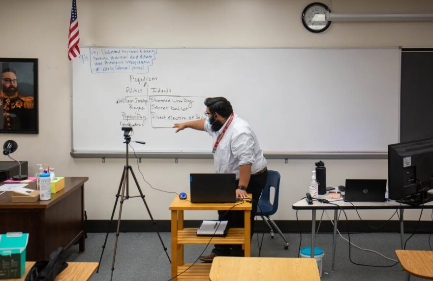 A male history teacher points to text written on a whiteboard as he teaches his remote students via a laptop.