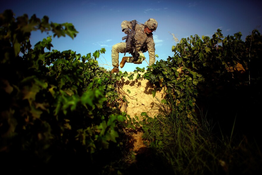 Pfc. James Turner with Bravo Company, 101st Airborne Division jumps over an 8-foot-high mud wall while navigating a grape field and trying to avoid walking on a heavily traveled path in the Pashmul District of Kandahar province in southern Afghanistan.