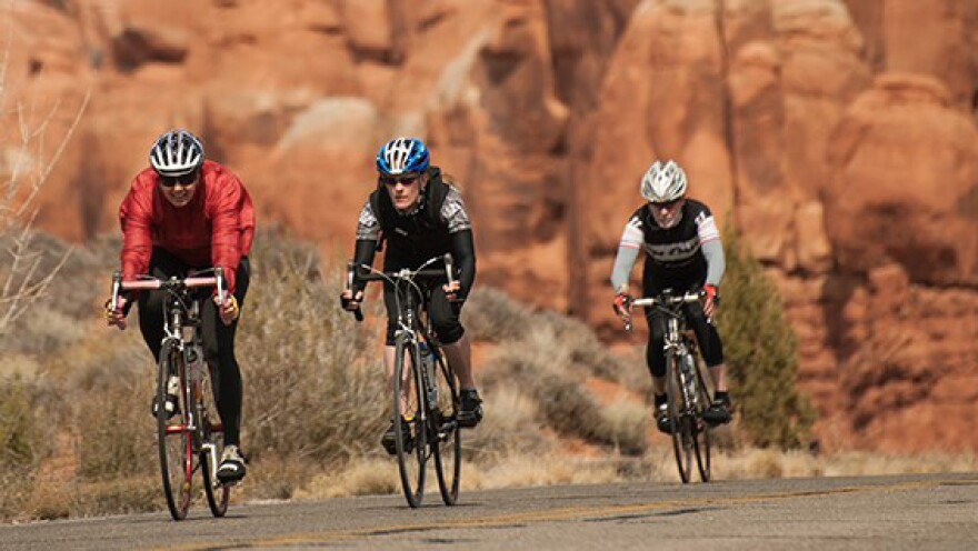 3 bikers cycle a road with a scenic red rock backdrop.