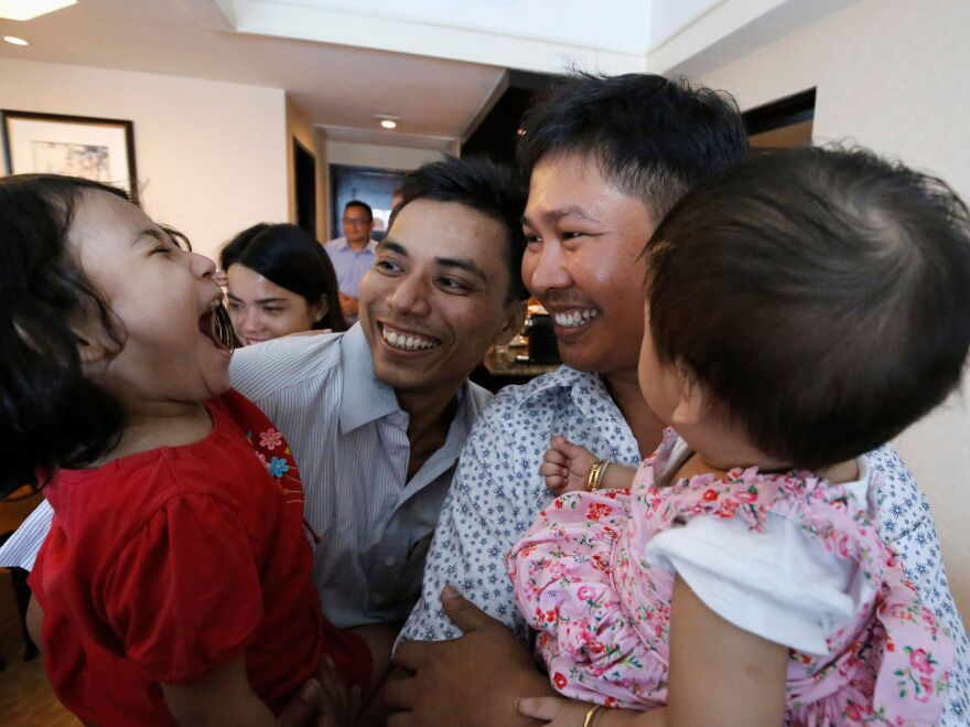 Reuters journalists Kyaw Soe Oo, left, and Wa Lone, right, with their children after being released from prison on Tuesday.