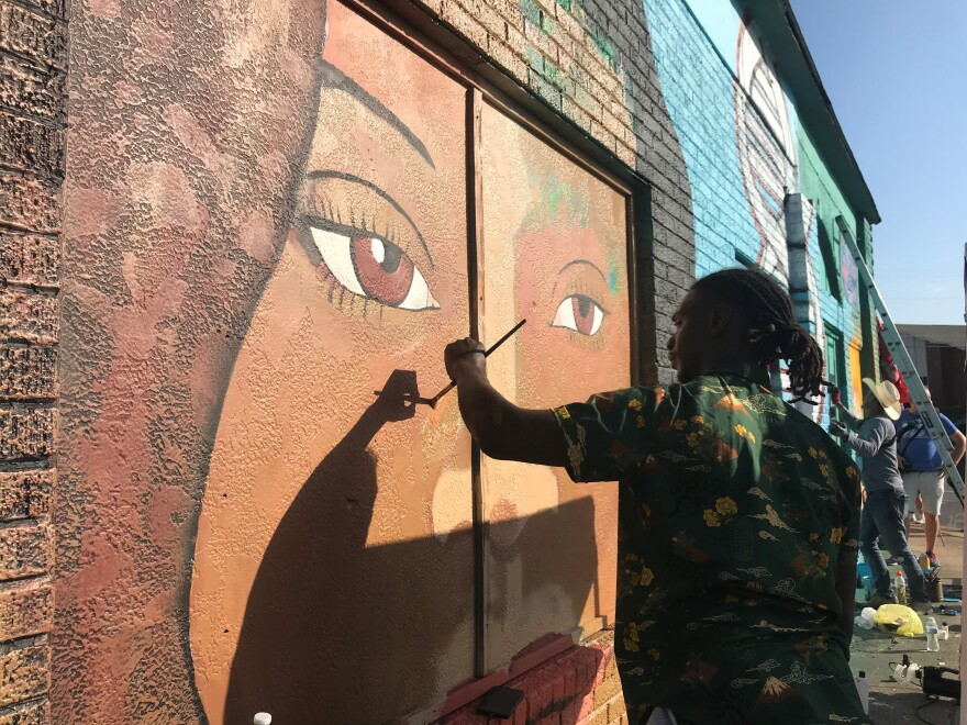 A dark-skinned man with short dreadlocks, tied back in a ponytail, uses a fine brush to paint Jefferson's face on the side of a brick building.
