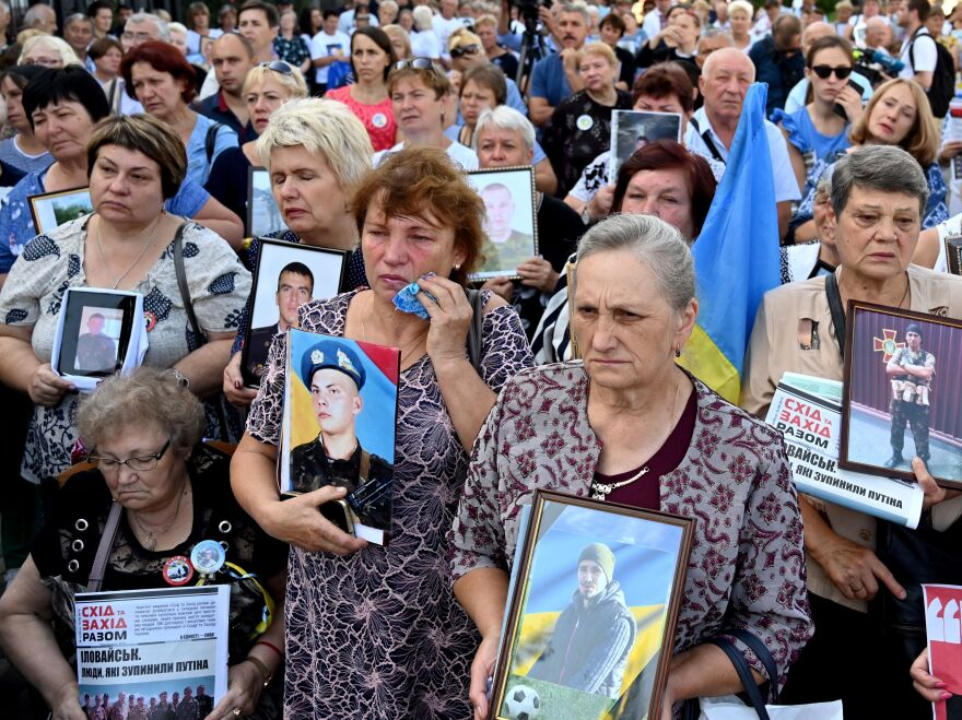 Mothers and widows of Ukrainian servicemen hold pictures of their relatives during a memorial rally in front of the Russian embassy in Kyiv, Ukraine's capital, in August.