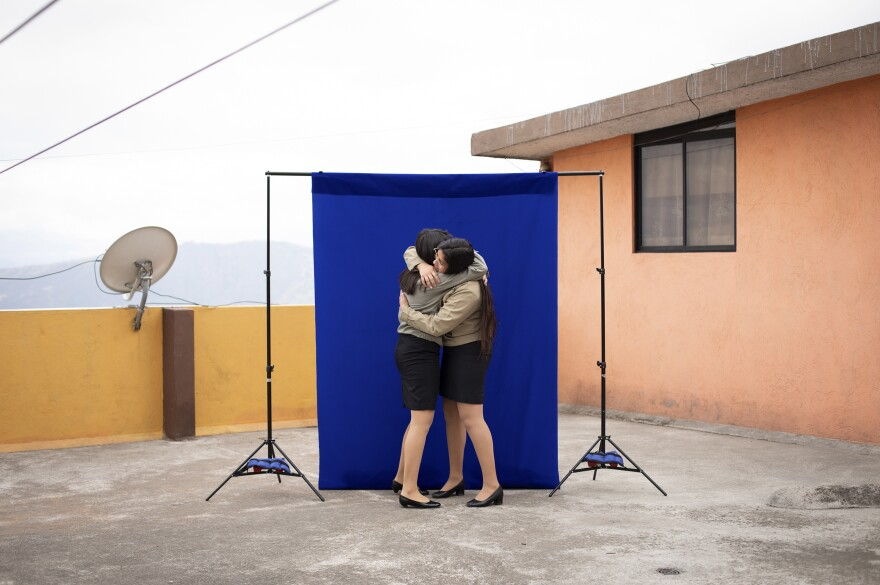 """Lisbeth Riera (left), 17, and Leslie Villacís, 18, hug during a pre-graduation portrait session at Leslie's house — the first time the friends had seen each other since a quarantine began four months earlier. The graduation ceremony is off this year """"I imagined that I was going to sing the hymn,"""" said Leslie, """"that I was going to hug everyone."""" <em>July 22. Quito, Ecuador.</em>"""