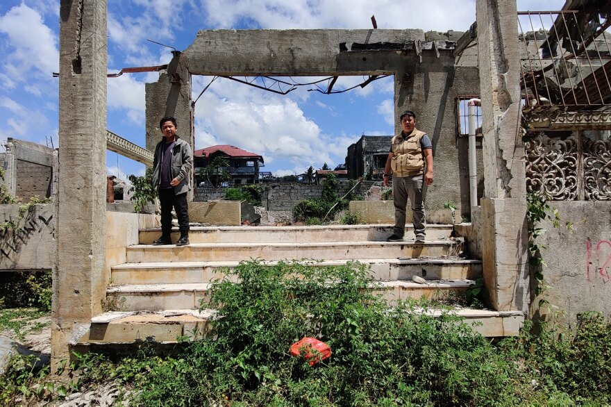 Zaqqir Ali Pacasum, 13, and Nawaz K. Lucman, 28 — Mustapha Alauya L. Pacasum's son and cousin, respectively — stand outside their destroyed ancestral home in Marawi City earlier this year.