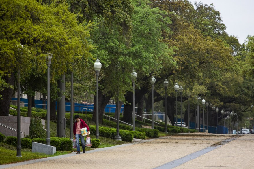 A man walks on the UT Austin campus with a pack of toilet paper and other supplies on March 16.