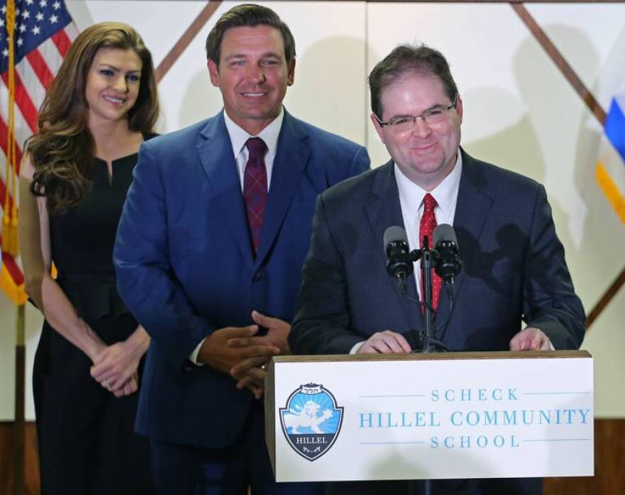 On Monday, Jan. 14, 2019, Judge Robert Luck, right, smiles and gives brief remarks after being selected to the Florida Supreme Court by Florida Gov. Ron DeSantis, center, standing next to his wife, Casey, left.