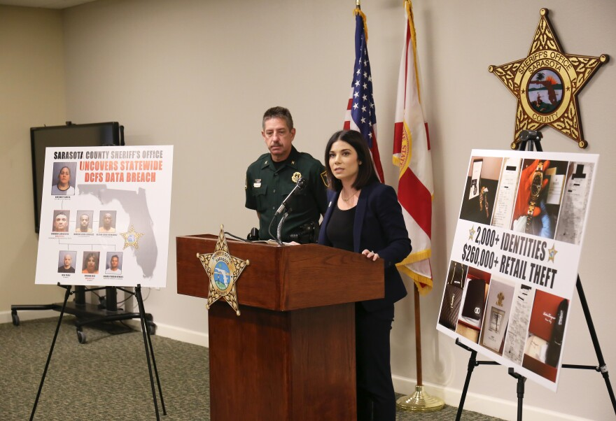 Department of Children and Family Services Assistant Secretary for Economic Self-Sufficiency Taylor Hatch and Sarasota County Sheriff's Office Colonel Kurt A. Hoffman stand at a podium in the Sheriff's media room to announce a data breach.