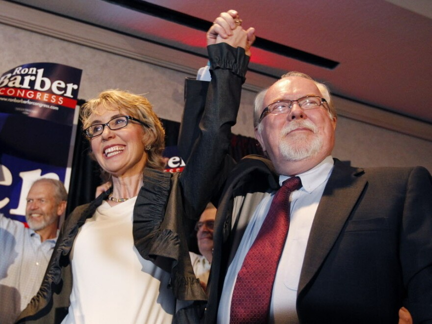 Former Rep. Gabrielle Giffords, left, celebrates with Ron Barber after he won Tuesday's special election in Arizona to serve the remaining seven months of her term. Like Giffords, Barber is a Democrat. He's also a former Giffords aide.