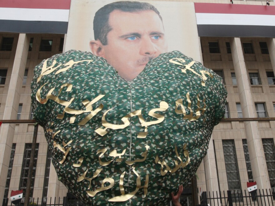Syrian demonstrators hold up a balloon for Valentine's Day in front of a portrait of President Assad, during a rally to show their support for their leader Damascus on Feb. 14, 2012. In the U.S., some fear that Valentine's Day has become serious business.