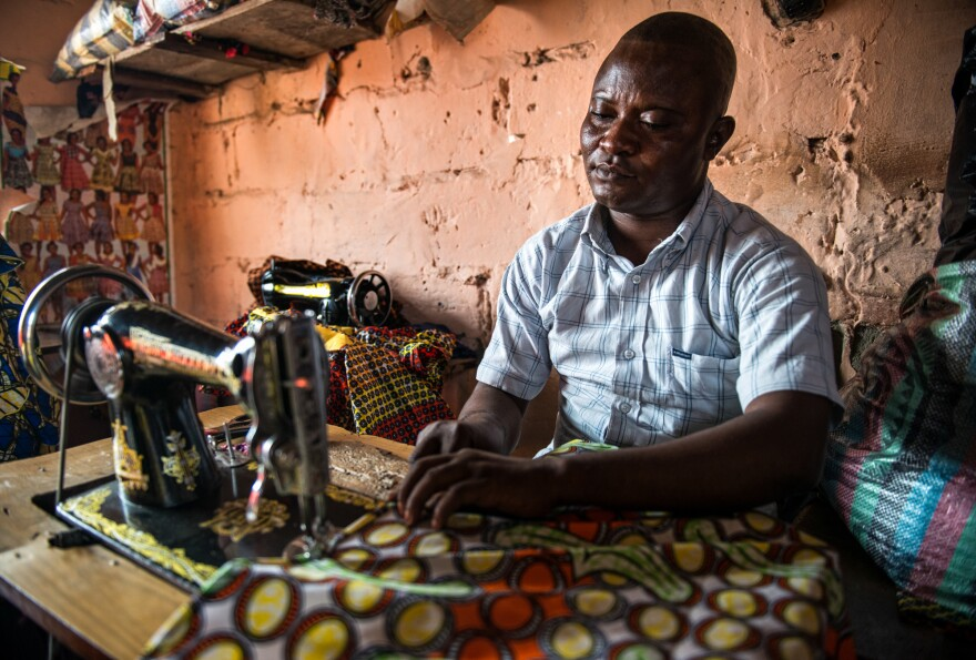 Gaby Ngabu Kasongo also has konzo. But his life has improved since he found a job as a tailor.