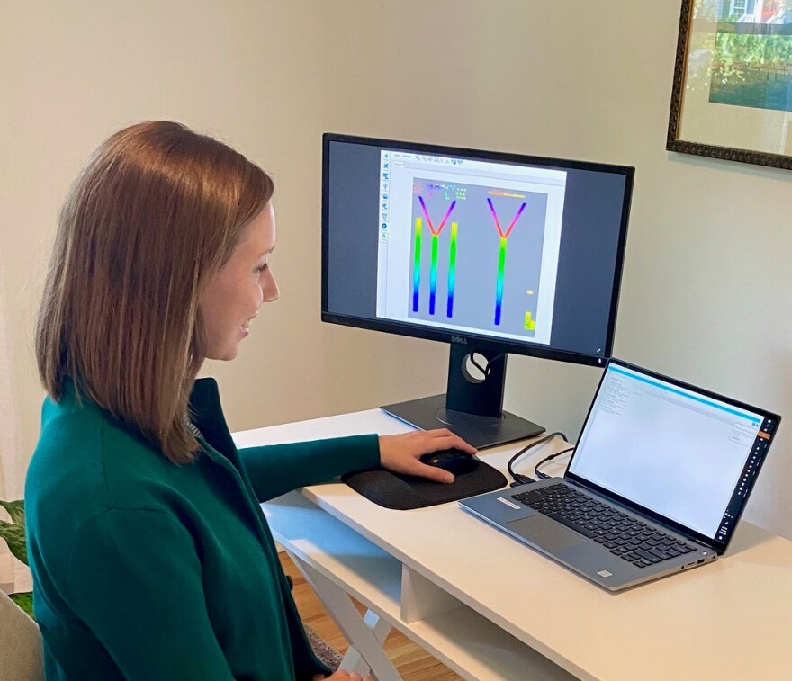 Kate Kopecky, a member of Wells Fargo's lighting committee, works from her home office to program the lights on the Duke Energy Center.