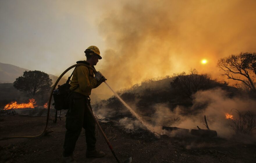 A firefighter battles a wildfire near Placerita Canyon Road in Santa Clarita, California, Sunday, July 24, 2016. (Ringo H.W. Chiu/AP)