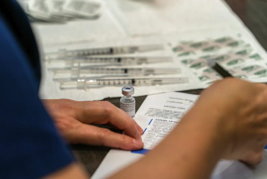 A nurse prepares paperwork, while a vial of the COVID-19 vaccine is visible next to her hand.